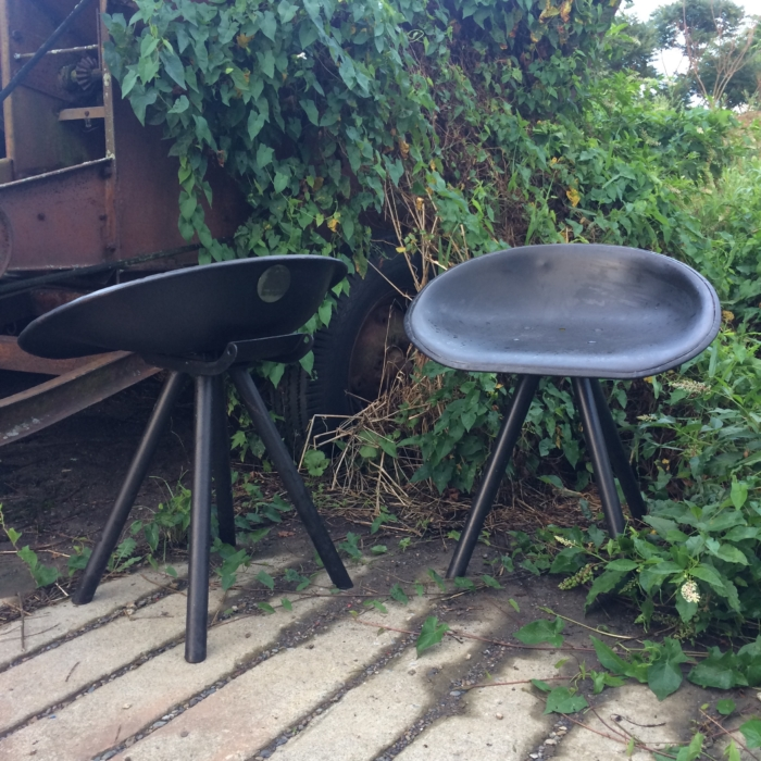 Set of two grey tractor seat chairs, steel tripod legs.